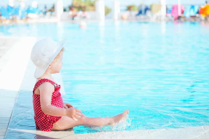 Baby sitting by swimming pool
