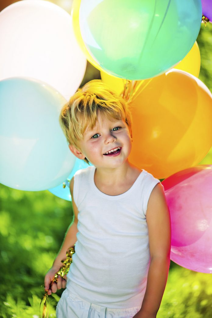 Cute boy with balloons in the park, iStock