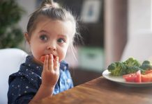 Little girl eating a plate of vegetables