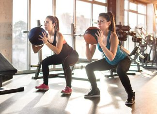 Two women squatting in gym