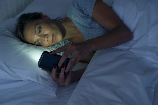 Woman-on-mobile-phone-in-bed