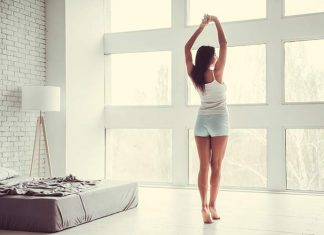 Woman stretching in bedroom