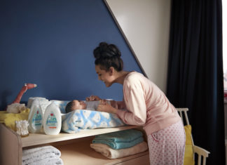 Mother changing baby's nappy