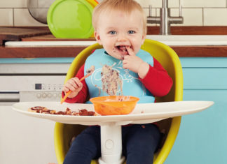 Messy baby eating food in high chair kitchen win a water wipes with soapberry bundle